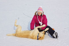 Girl on ice skates playing with dog Stock Image