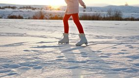 Girl ice skating on lake against setting sun stock video footage