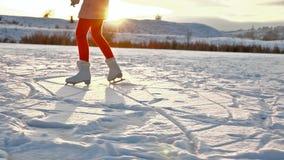 Girl ice skating on lake - slow motion. Girl ice skating on lake against setting sun - slow motion stock video footage