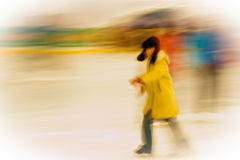 Girl ice-skating outside. A young girl wearing a yellow coat and winter hat as she ice-skates at an outdoor rink. rn Royalty Free Stock Photography