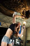 Girl with an ideal body inspecting car on hydraulic lift. Girl with an ideal body and with a lantern in her hand inspecting a car on hydraulic lift in a car Stock Photos