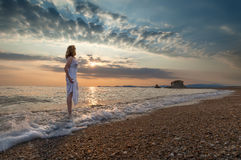 Girl on idyllic beach in waves at beautiful sunrise