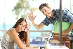 Girl ignoring a stalker man waving. Girl ignoring and rejecting to a stalker men waving her in a coffee shop in a blind date Stock Photography