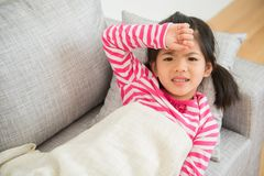 Girl with illness and hand on her head. Little asian chinese girl with illness and hand on her head feel unwell on sofa in the living room at home. family Stock Photography