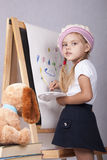 The girl in the image of the artist draws on the easel. Four-year-old girl playing in the artist and draws on the easel-painting. In the arms of children brush royalty free stock images