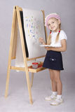 The girl in the image of the artist draws on the easel Stock Photos