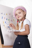 The girl in the image of the artist draws on the easel Stock Photo