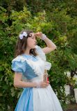 The girl in image of fabulous heroine Alice looks into distance. And holding a magic drink cherry color of the glass medical bottle with a label that says drink Stock Images