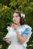 Girl in the image of the fabulous heroine is drinking tea. In the garden Royalty Free Stock Photos