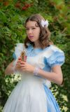 Girl in image of fairy tale heroine drinks drink of glass bottle. Girl in the image of fairy tale heroine drinks the drink of glass bottle cherry color with a Stock Image