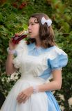 Girl in image of fairy tale heroine drinks drink of glass bottle. Girl in the image of fairy tale heroine drinks the drink of glass bottle cherry color with a Stock Photo
