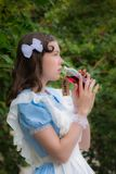Girl in image of fairy tale heroine drinks drink of glass bottle. Girl in the image of fairy tale heroine drinks the drink of glass bottle cherry color with a Royalty Free Stock Photography