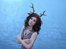 Girl in the image of a faun, costume and make-up of a deer, a fantastic character of the spirit of forest in brown dress royalty free stock photos