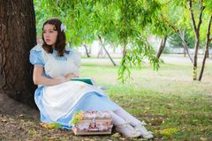 Girl in the image of the heroine of a fairy sitting under a tree. Girl in the image of a character from a fairy tale is sitting under a tree with a book Stock Photo