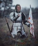 Girl in image of Jeanne d`Arc in armor kneels with flag in her hands and sword on meadow. Girl in image of Jeanne d`Arc in armor kneels with flag in her hands royalty free stock photography