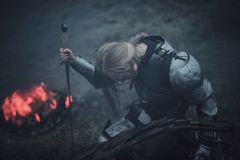 Girl in image of Jeanne d`Arc in armor and with sword in her hands kneels against background of fire and smoke. Girl in image of Jeanne d`Arc in armor and with Stock Photos