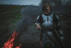 Girl in image of Jeanne d`Arc in armor and with sword in her hands stands against background of fire and smoke. Girl in image of Jeanne d`Arc in armor and with Stock Photos