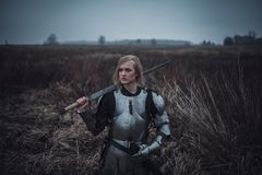 Girl in image of Jeanne d`Arc in armor and with sword in her hands stands on meadow. Closeup. Girl in image of Jeanne d`Arc in armor and with sword in her hands Royalty Free Stock Photography