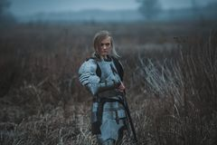 Girl in image of Jeanne d`Arc in armor and with sword in her hands stands on meadow. Back view. Girl in image of Jeanne d`Arc in armor and with sword in her Royalty Free Stock Image