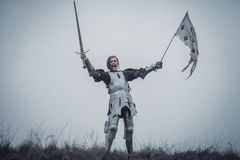 Girl in image of Jeanne d`Arc stands in armor and issues battle cry with sword raised up and flag in her hands. Girl in image of Jeanne d`Arc stands in armor stock image