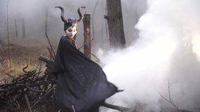 The girl in the image of Maleficent is on a background of smoke in the forest