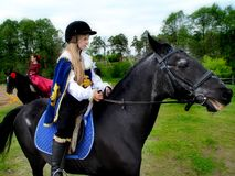 Girl in the image of Musketeers on horseback. Royalty Free Stock Photography