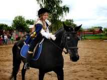 Girl in the image of Musketeers on horseback. Royalty Free Stock Image