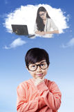 Girl imagines a businesswoman. Beautiful little girl wearing glasses and imagines a businesswoman working with laptop on the thought bubble royalty free stock image