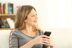 Girl imagining and holding a smart phone. Sitting on a sofa in the living room in a house interior Stock Photo