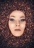 Girl immersed in coffee beans Stock Images