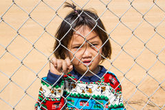 Girl imprison. Girl behind the metal fence royalty free stock images