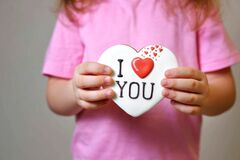 Free Girl In A Pink T-shirt Holds A Gingerbread Valentine Card. Gift For Valentine`s Day. Congratulations Royalty Free Stock Image - 209657396