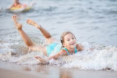 Free Girl In A Turquoise Bathing Suit In The Sea, Happy Children Swimming In The Sea, Waves And Splashes From Swimming In The Sea Stock Photos - 163265323