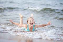 Free Girl In A Turquoise Bathing Suit In The Sea, Happy Children Swimming In The Sea, Waves And Splashes From Swimming In The Sea Stock Images - 163265364