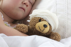 Girl In Bed Cuddling A Teddy With Bandage Stock Images