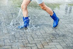 Girl In Blue Rubber Boots Jumping In A Puddle After A Rain Royalty Free Stock Photography
