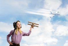 Girl In Helmet Pilot Playing With A Toy Airplane Royalty Free Stock Photography