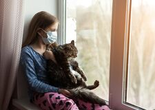 Girl In Medical Mask Holding Cat And Suffering From Allergy At Home Royalty Free Stock Image