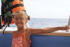 Free Girl In Orange Dress With Life Jacket Weighing Behind Her Head Takes Walk On Boat Royalty Free Stock Photography - 163622627