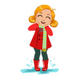 Girl In Red Coat And Rubber Boots, Kid In Autumn Clothes In Fall Season Enjoyingn Rain And Rainy Weather, Splashes And