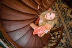 Free Girl In Silk Robe Stand On Wooden Spiral Staircase Royalty Free Stock Photography - 137764307