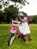 Girl In The Garden Riding Her Cycle Stock Images