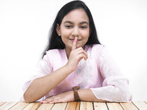 Girl with index finger on her lips Stock Photography