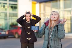 Girl with indignant screams holding a broken smartphone, guy is standing from behind and clinging to head. A young European couple stand on the street, a girl royalty free stock images