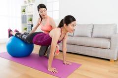 Girl with individual tutor using yoga ball workout. Young smiling girl with individual home tutor using yoga ball workout in living room and training personal stock photos
