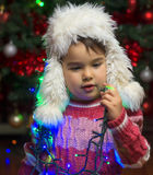 Girl indoor on christmas day playing with tree lights Royalty Free Stock Photo
