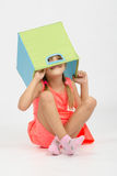 Girl indulging in a box for toys put on the head Royalty Free Stock Photography