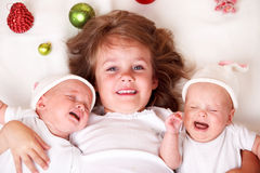 Girl and infant twins. Christmas toddler girl and infant twins Stock Images