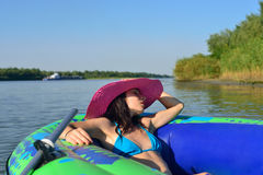 Girl on an inflatable boat in a hat Stock Photography