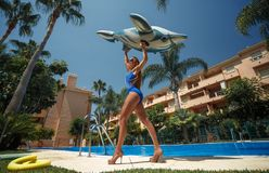 Girl with inflatable dolphin. Tan girl sits on inflatable dolphin in the pool stock photo